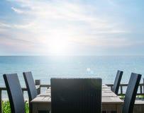 Vintage efectuado en el ajuste de la tabla en el restaurante de la playa, con la opinión del mar fotografía de archivo
