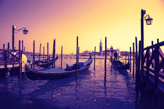 Vintage effect of beautiful gondolas docked to the poles on the Grand Canal in Venice Royalty Free Stock Photography