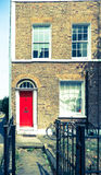 Vintage effect East London terrace home with red door. Royalty Free Stock Image