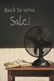 Vintage electric fan on table. Vintage electric fan with book on table royalty free stock image