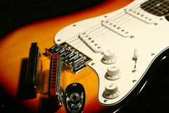 Vintage electric guitar with harmonica on black background Royalty Free Stock Image