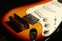Vintage electric guitar with harmonica on black background Stock Photo