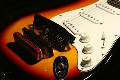 Vintage electric guitar, harmonica, sunglasses on black background Royalty Free Stock Images