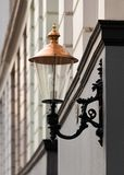 Vintage electric lantern with copper top and ornate fixture. On the facade of classic residential building royalty free stock photo