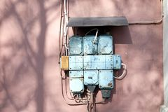 A vintage fuse box on a pink wall. Vintage electricity circuit box, blue on a pink wall, old engineering technology. High voltage stock photo