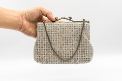Vintage elegance handbag decorated with diamond isolated on whit. Woman hand holding vintage elegance handbag decorated with diamond isolated on white background Royalty Free Stock Photography