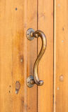 Vintage elegant curved handle on wooden door. Forged parts of the exterior Royalty Free Stock Images
