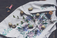 Vintage embroidery, wooden thread spools and quail eggs Royalty Free Stock Images