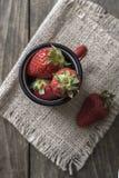 Vintage enamel mug filled with fresh strawberries Stock Photos