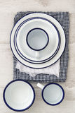 Vintage enamelware crockery on retro cloths on rustic wooden bac Royalty Free Stock Images