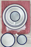 Vintage enamelware crockery on retro cloths on rustic wooden bac Stock Images