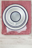 Vintage enamelware crockery on retro cloths on rustic wooden bac Stock Photos