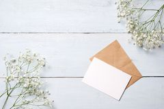 Vintage envelope with flowers on light blue wooden background. Banner mockup for womans or mother day, wedding invintation, easter. Card. Flat lay, top view royalty free stock photo