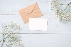 Vintage envelope with flowers on light blue wooden background. Banner mockup for womans or mother day, wedding invintation, easter. Card. Flat lay, top view royalty free stock image