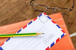 Vintage envelope, pencils, notebook and glasses on a wood floor Stock Photo