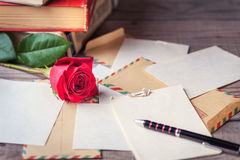 Vintage envelopes, red rose and sheets of paper scattered on wooden table for writing romantic letters. Stock Images