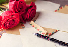 Vintage envelopes, red rose and sheets of paper scattered on the wooden table for writing romantic letters. royalty free stock image
