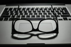 Vintage eye glasses on laptop trackpad low key light Stock Photography