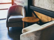 Vintage fabric armchair with round wooden table near the wall, concrete, black steel and wooden wall royalty free stock images