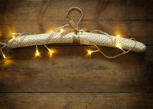 Vintage fabric hanger with gold Christmas warm gold garland lights on wooden rustic background. filtered image Royalty Free Stock Image