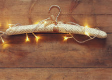 Vintage fabric hanger with gold Christmas warm gold garland lights on wooden rustic background. filtered image Royalty Free Stock Images