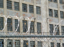 Vintage factory behind razor wire and link fence Royalty Free Stock Photography