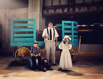 Vintage Family Going on Travel Vacation. An old fashioned vintage family is waiting in an old train station by a luggage cart for a vacation or travel concept stock photo