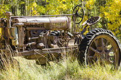 Vintage Farm Tractor. A rusty old farm tractor sits alone in the field on a farm in Colorado in the fall stock photo