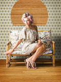 Vintage Fashion Photo Of A Sexy Blond Woman. Sexy Fashion Photo Of Beautiful Girl Wearing Hair Rollers Sitting On A Vintage Floral Sofa In A Depiction Of Pinup Stock Photography