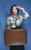 Vintage fashion retro brunette girl going on journey woman with. Suitcase on blue background Stock Photography