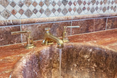 Vintage faucet in marble bathroom. Royalty Free Stock Image