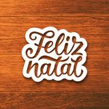 Vintage Feliz Natal typographic vector poster. Feliz Natal portuguese Merry Christmas text on white paper cut style label over wood background. Lettering for Stock Photos