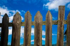 Vintage fence of old wooden planks against the blue sky. Background concept stock images