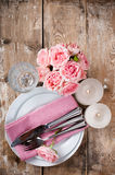 Vintage festive table setting with pink roses. Candles and cutlery on an old wooden board Stock Photo