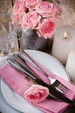 Vintage festive table setting with pink roses. Candles and cutlery on an old wooden board Royalty Free Stock Images