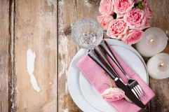 Vintage festive table setting with pink roses. Candles and cutlery on an old wooden board Royalty Free Stock Image