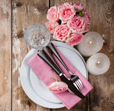 Vintage festive table setting with pink roses. Candles and cutlery on an old wooden board Royalty Free Stock Photo