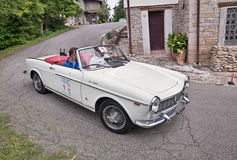 Vintage Fiat 1500 Pininfarina Cabriolet (1966). Driver and co-driver on a vintage Fiat 1500 Pininfarina Cabriolet (1966) in classic car rally Coppa cittá di Stock Images