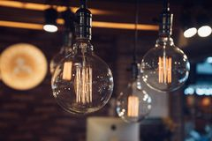 Vintage filament lamp with coil shape light hanging from the ceiling of dark background.  royalty free stock image