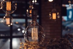 Vintage filament lamp with coil shape light hanging from the ceiling of dark background.  royalty free stock images