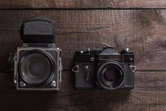 Vintage film camera. Vintage black film camera on the brown background of natural wood with the lens Royalty Free Stock Image