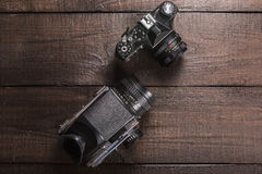 Vintage film camera. Vintage black film camera on the brown background of natural wood with the lens Stock Images