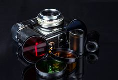 Vintage film camera, film cassettes and color filters on a dark background. Selective focus stock images