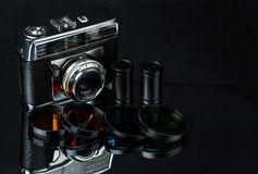 Vintage film camera, film cassettes and color filters on a dark background.  stock images