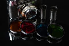 Vintage film camera, film cassettes and color filters on a dark background. Selective focus royalty free stock images