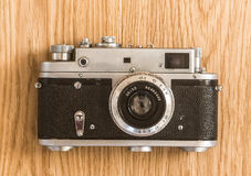Vintage film camera oak background. Vintage rangefinder film analog Leica style camera with standard 50 mm lens. Leica thread mount 39 mm. Logo and brand name Royalty Free Stock Image