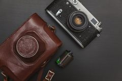 Old film camera and a roll of film. Vintage Film Camera And Roll On Black Wooden Background Technology Development Photographer Concept. Top View Stock Photography