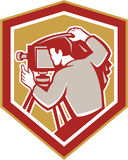 Vintage Film Camera Shield Retro. Illustration of a vintage movie film camera with photographer setting it up set inside shield crest shape done in retro woodcut Royalty Free Stock Photo