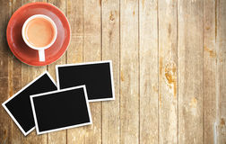 Vintage film camera and two blank photo frames on wooden table. Cup of coffee and two blank photo frames on wooden table. Top view with copy space for design Royalty Free Stock Image
