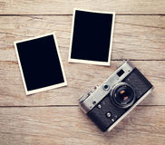 Vintage film camera and two blank photo frames. On wooden table. Top view Stock Photos